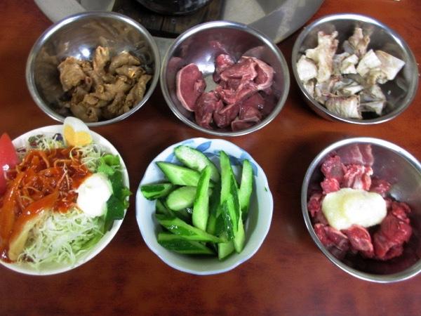 さらに食べる。左上からホルモン、タン、軟骨、サラダ、キューリ、バクダン。人気の「バクダン」は緬羊のニンニク和え