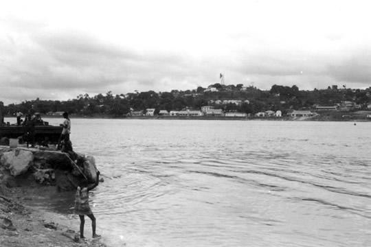 岸辺では子供が魚を釣っている